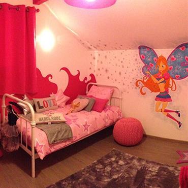 Chambre enfant aux teintes roses. Dessin d'une fée sur le mur. Lit métallique blanc