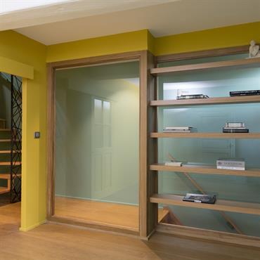 Bibliothèque et baie vitrée dans la chambre laissent apparaître le mélange de couleurs