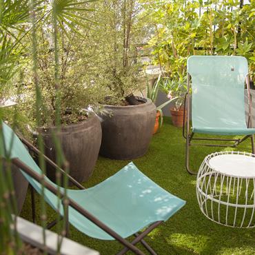 Charmante terrasse avec jardinières et chaises longues pliantes