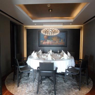 Salle à manger dans un style classique. Table ronde pour 9 couverts posée sur un tapis rond et surmonté d'un lustre. Nature morte sur le mur du fond.