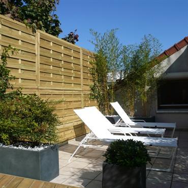 Terrasse paysagée avec jardinières, fermée par une palissade en bois pour profiter de l'extérieur en toute tranquilité.