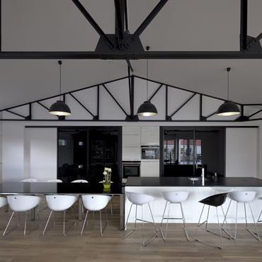La cuisine ouverte sur la pièce de vie a été conçue avec de grandes portes coulissantes en verre noir permettant de dissimuler complètement les rangements et la table de cuisson