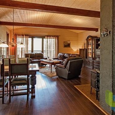 Pièce à vivre au mobilier ancien et revêtements en bois. Parquet et lambris. Poutres apparentes.