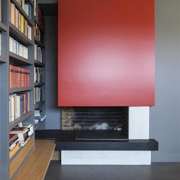 Bibliothèque contemporaine intégrant la cheminée. Peintures grise et rouge