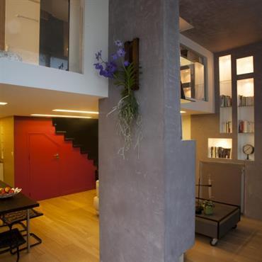 La mezzanine est soutenue par un pilier structurel, dont le parti pris a été d'en faire une  sculpture fonctionnelle en réalisant une bibliothèque déstructurée en béton gris et tempérée ...