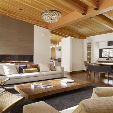 Pièce à vivre chaleureuse grâce au plafond en bois et à la décoration sobre