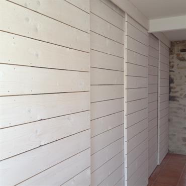 Dressing aux portes coulissantes en lattes de bois blanc