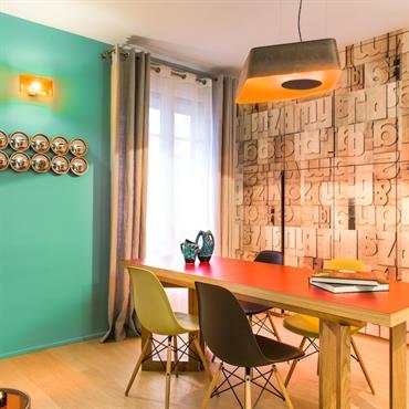 Derrière la table de salle à manger, mur de rangements avec papier peint graphique en relief