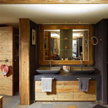 Salle de bain moderne dans une ambiance chalet. Lavabos double vasque sur meuble en bois brut
