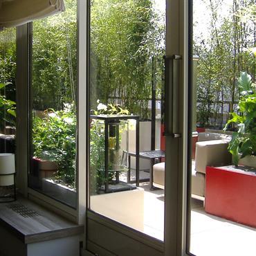Terrasse avec grande baie vitrée et plantes vertes