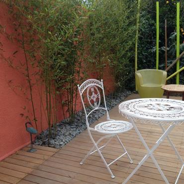 Jardin de ville moderne avec bambous, terrasse en acacia et mobilier de jardin en fer blanc