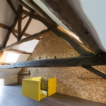 Aménagement des combles : on a gardé les poutres et le mur de pierre authentiques et ajouté de la modernité avec l'escalier jaune