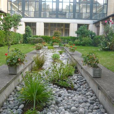 Aménagement du jardin d'agrément du lycée Montaigne à Paris avec bassin de galets