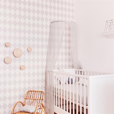 Le papier peint gris et blanc sur un mur apporte un effet déco à cette chambre de bébé douce et chic.