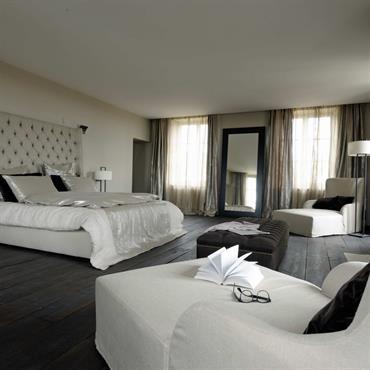 Chambre avec parquet en bois noir. Parure de lit et fauteuils blancs