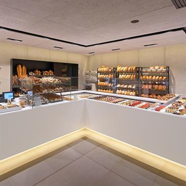 Projet d'agencement d'une chocolaterie haut de gamme dans la région de Bruxelles ; il y a plusieurs bancs pour étaler des produits et des Panbeton® pour l'habillement des murs.  Produit : ...