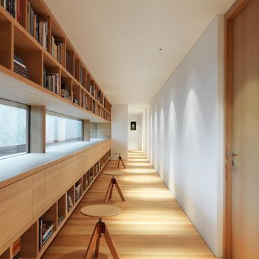 Couloir aménagée en longue bibliothèque. Cadrage sur le paysage par des fenêtres en bandeau.