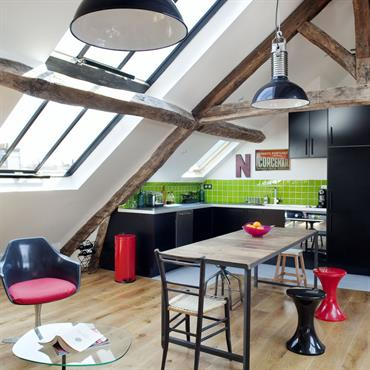 La cuisine du loft au volume exceptionnel exploite le charme de son ossature ancienne avec ses poutres apparentes conservées dans leur état brut. Une grande verrière de style industriel ouvre ...