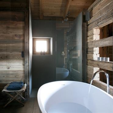 Entre rusticité et design, la salle de bain apporte le luxe des équipements dernière génération comme cette grande baignoire îlot.