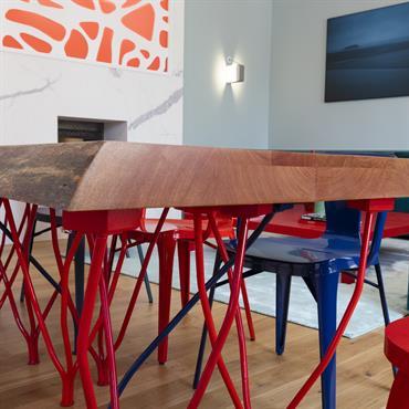 Table design avec pieds en métal rouge travaillé et plateau en bois massif