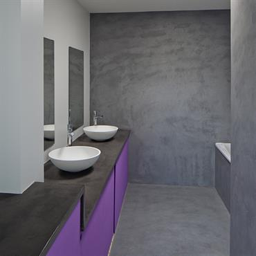 Salle de ban enduit béton. Meubles violets, lumière zénithale