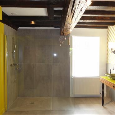 Modernisation de cette salle de bain à poutres apparentes avec une dominante jaune