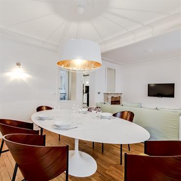 La grosse suspension design au-dessus de la table et des chaises matérialise le coin salle à manger.