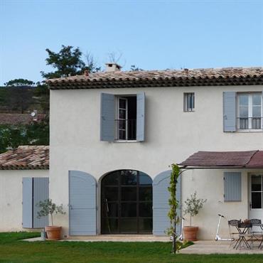 La façade traditionnelle arbore un enduit blanc lissé, des volets en bois bleus et un toit aux tuiles provençales vieillies.