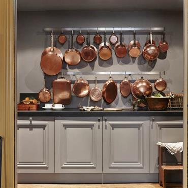 La cuisine entièrement équippée se loge derrière une double porte coulissante.