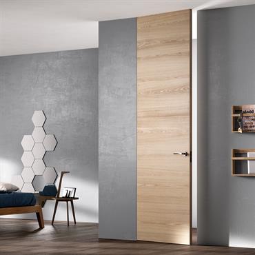 Chambre avec murs béton et porte en bois