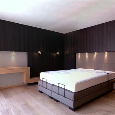 Chambre double contemporaine à lits motorisés. Parquet, étagère et chevets chêne clair en contraste avec le bois sombre des parois verticales.