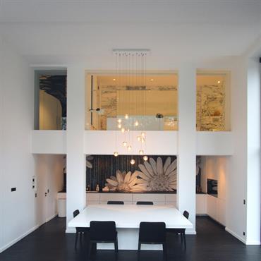 Salle à manger avec parquet en bois sombre et grande hauteur sous plafond