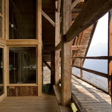 Terrasse  extérieure aménagée à l'intérieur du volume de la charpente, donnant sur les anciennes coursives,