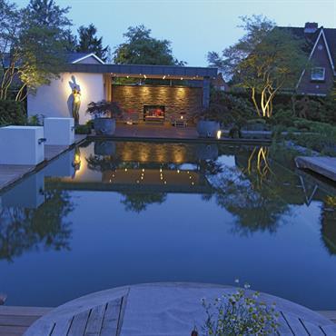 Le jardin avec, en son centre, une piscine naturelle, présente tout ce qu'un client exigeant recherche : patio et terrasse, matériaux naturels et installations extérieures.