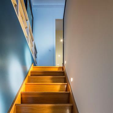 Escalier en bois jaune en contraste avec les murs bleus