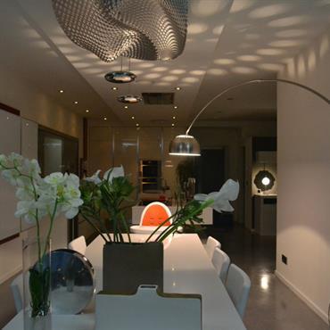 Salle à manger intimiste par la lumière tamisée. Luminaire en métal perforé.