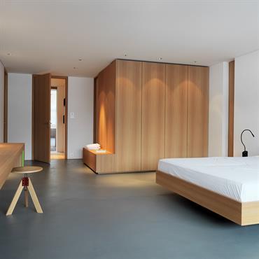 Grande suite parentales. Espace bureau face au lit, salle de bain derrière le dressing. Mobilier en bois, sol en linoléum.
