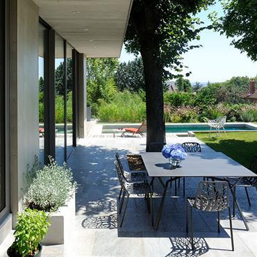 Terrasse ombragée dallée, avec table d'extérieur en métal