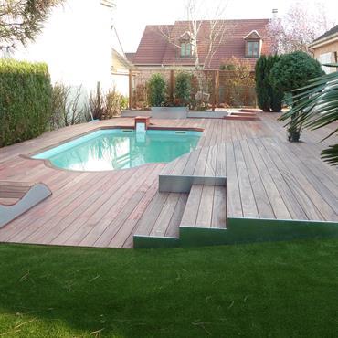 Terrasse en bois exotique avec piscine. L'ensemble de la terrasse habillée de bois de padouk. Deux assises ont été construites sur mesure en padouk.