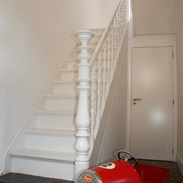 Carrelage ancien en contraste avec les murs et escalier blanc