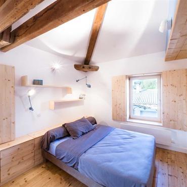 Chambre blanche avec poutres apparentes et rangement en tête de lit