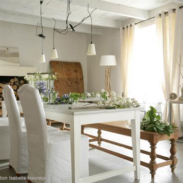 Salle à manger lumineuse qui met en scène le bois dans un esprit campagne. Plafond blanc aux poutres apparentes, table de salle à manger en bois peint en blanc, banc ...