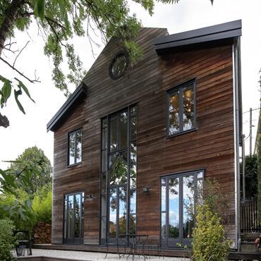 Pour atténuer son coté massif, la maison est comme posée sur une terrasse suspendue. Les graviers blancs illuminent le bardage en redcedar de la maison. les marches d'escalier en graviers ...