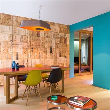 Derrière la table de salle à manger, le mur équipé de rangements est habillé d'un papier peint en relief effet lettres d'imprimeur.