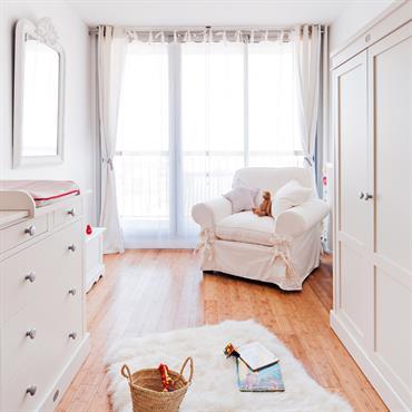Dans cette chambre de bébé à la lumière tamisée par un voilage aux fenêtres, les meubles en bois peint, le parquet en bambou et le gros fauteuil romantique blanc contribuent ...