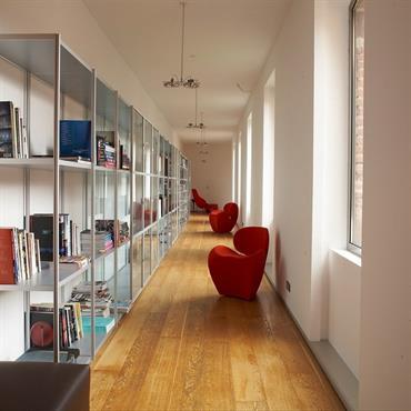 Couloir de belle taille équipé d'étagères en verre pouvant servir de bibliothèque. La largeur du couloir invite à optimiser cet espace lumineux.