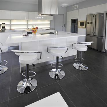 Dans le plus pur du style contemporain, la cuisine offre une blancheur immaculée, depuis les meubles laqués blancs jusqu'aux plans de travail.