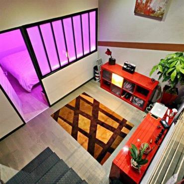 Eclairage rose dans la chambre en contrebas. La verrière diffuse cette lumière dans la pièce à vivre