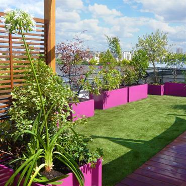Coin jardin aménagé sur ce balcon, avec gazon artificiel et jardinières violettes qui donnent du peps