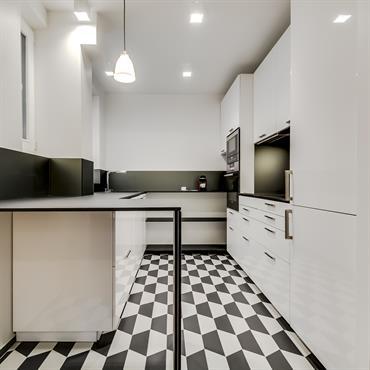 Petite cuisine en longueur en noir et blanc : placards blancs, plans de travail noirs et carrelage géométrique noir et blanc.